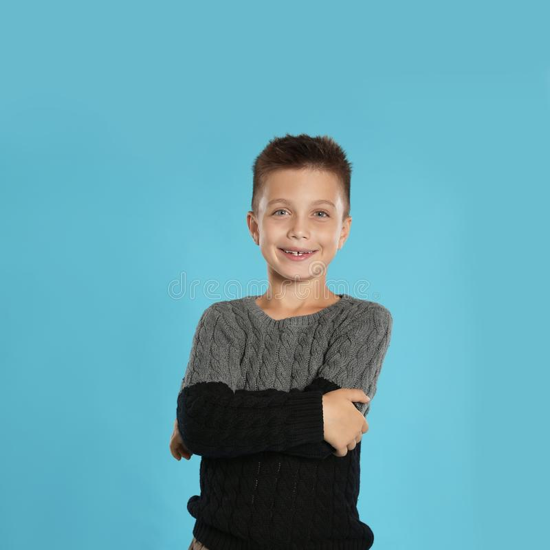 Cute little boy in warm sweater, space for text. Winter season. Cute little boy in warm sweater on blue background, space for text. Winter season royalty free stock image