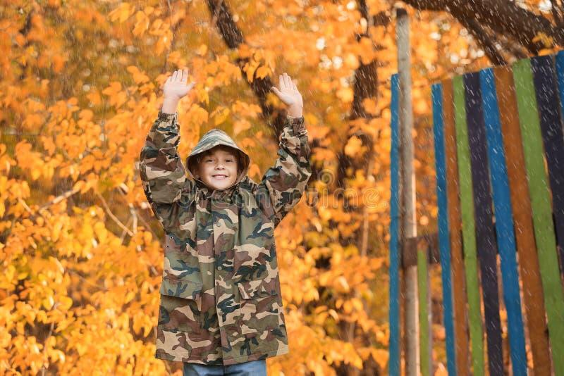 Cute little boy wearing raincoat in autumn park stock photography