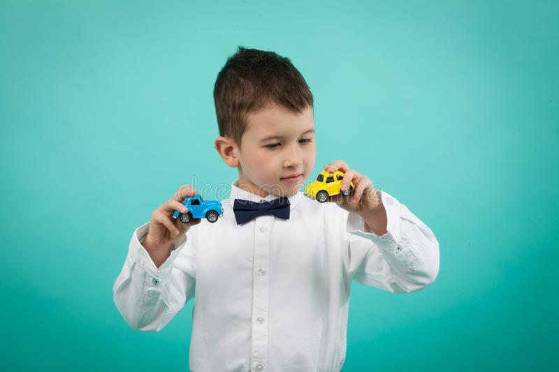 Cute little boy with white shirt and bow tie, playing with cars toy royalty free stock photography