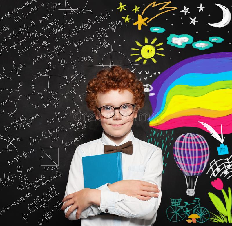 Cute little boy in white shirt and bow tie posing in front of blackboard. Portrait of smart male child. Smiling school boy royalty free stock image