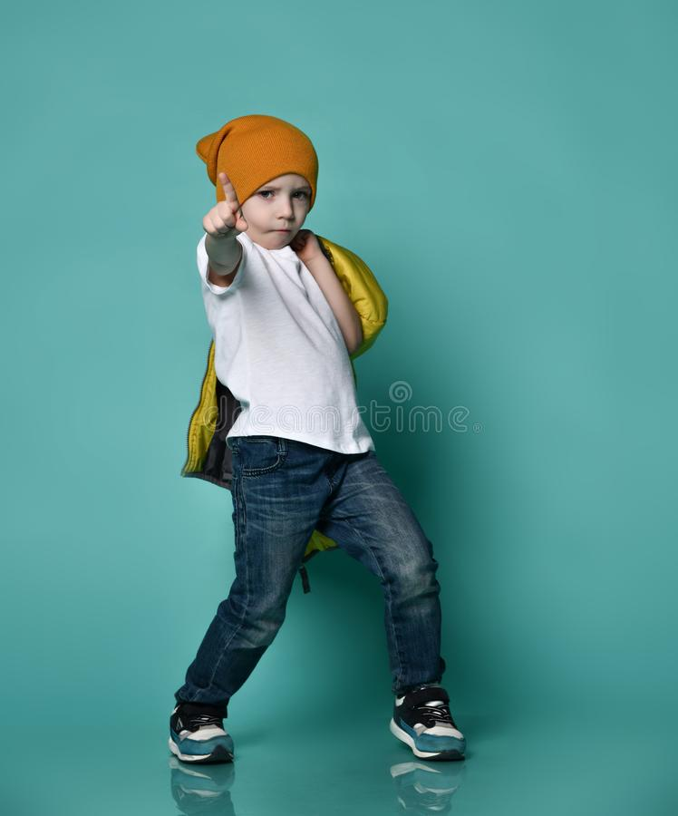 Cute little boy in white T-shirt, hat and jacket in his hand posing in front of green blue wall. stock photo