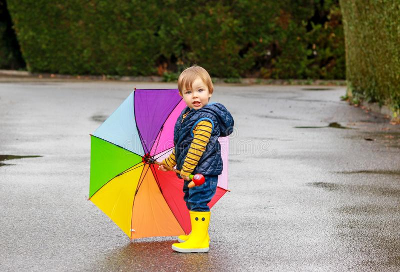 Cute little boy in yellow rubber boots with colorful rainbow umbrella staying on wet road looking at camera. After rain. stock image