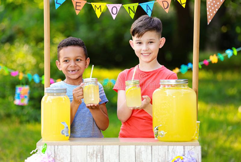 Cute little boys at lemonade stand. Summer refreshing natural drink stock photos