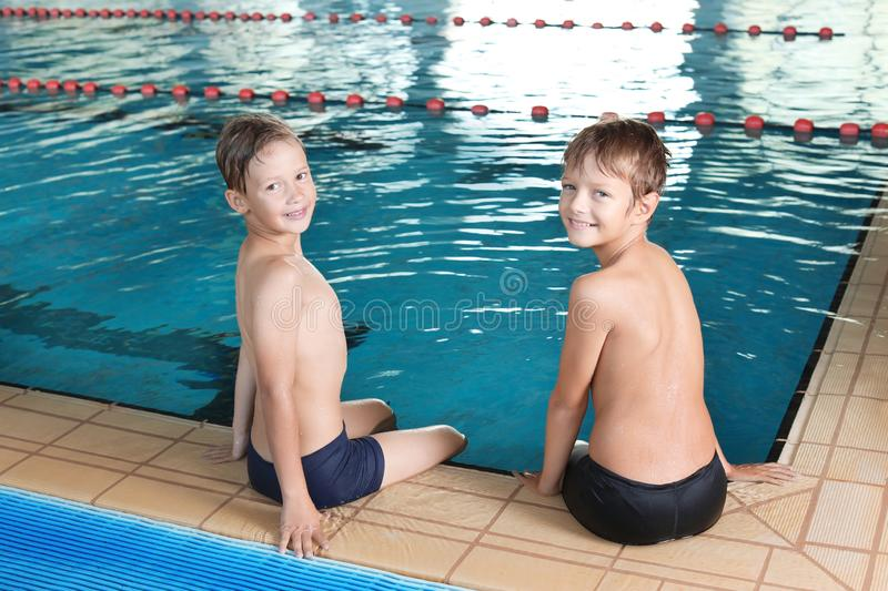 Cute little boys near indoor pool stock images
