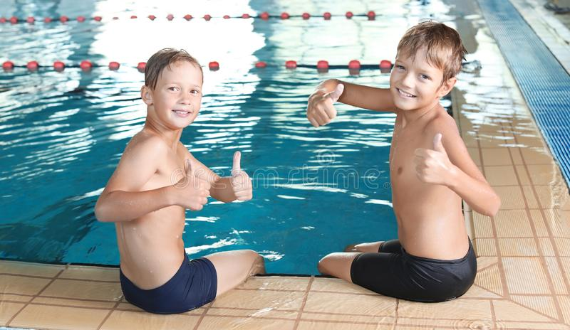 Cute little boys near indoor pool royalty free stock image