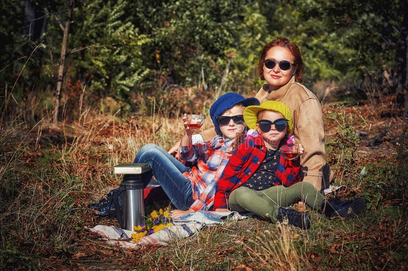 Cute little brother with sister with mom at an autumn picnic. Children on vacation in nature on an autumn day . Camping in the woods . Family holiday. Children stock photos