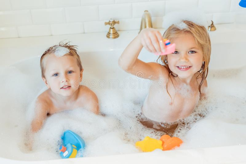 cute little brother and sister playing with toys and smiling at camera royalty free stock image