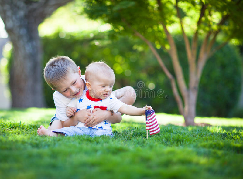Cute little brothers sitting on a green lawn holding American flag stock photos
