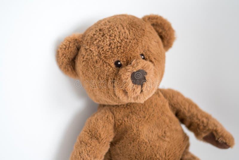 Cute little brown teddy bear on a white wall. Cute little brown bear on a white wall waiting for a company stock photos