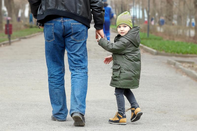 Cute little caucasial boy with blue eyes looks back walking with man, holding him with hand. Stroll in autumn park, casual wear, m stock photo
