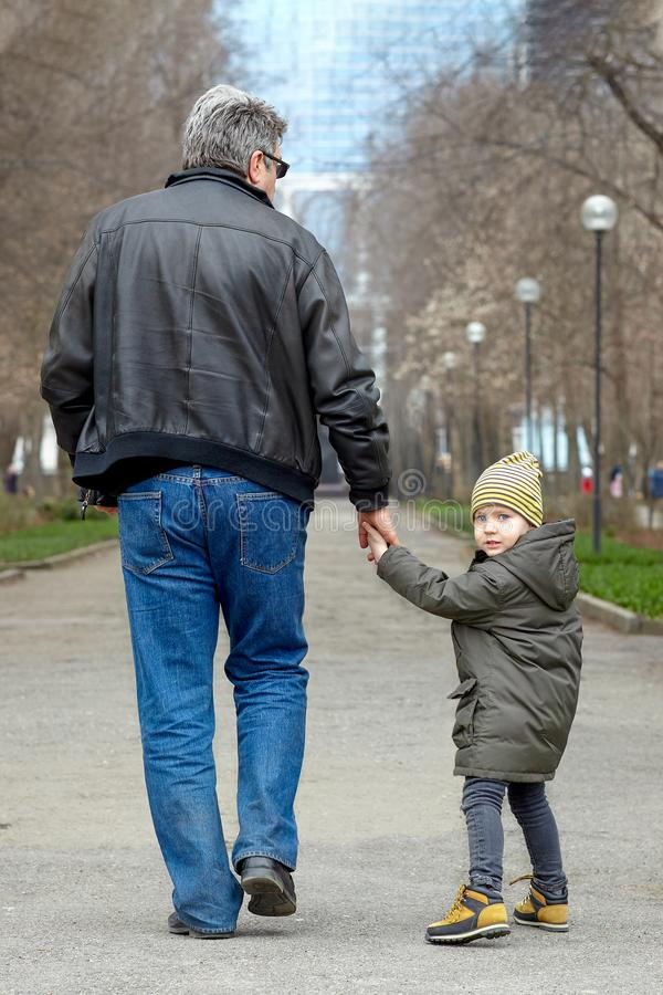 Cute little caucasial boy with blue eyes looks back walking with old-aged man, holding him with hand. Stroll in autumn park, casua stock image