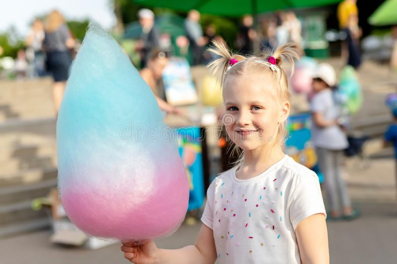 Cute little caucasian blond kid girl holding in hand stick with Bright big multicolored cotton candy sweet at city park during royalty free stock photography