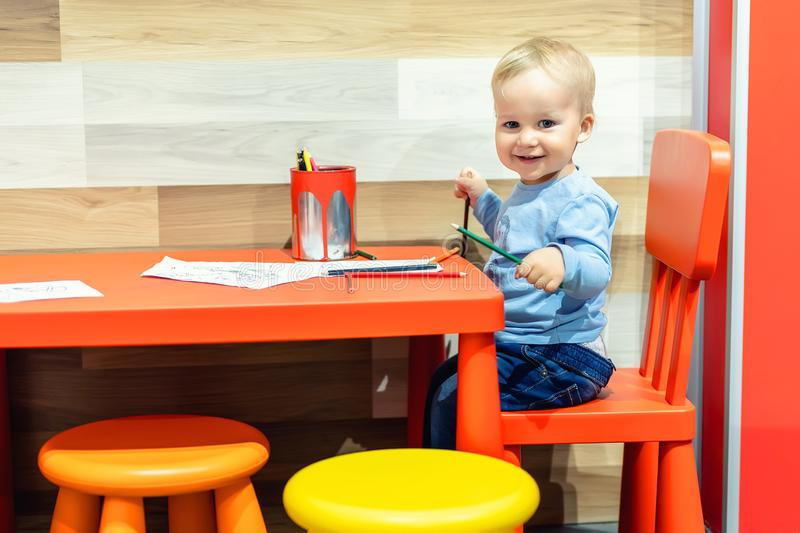 Cute little caucasian blond toddler boy sitting at table and drawing at children area at retail clothes store. Baby spending time stock images