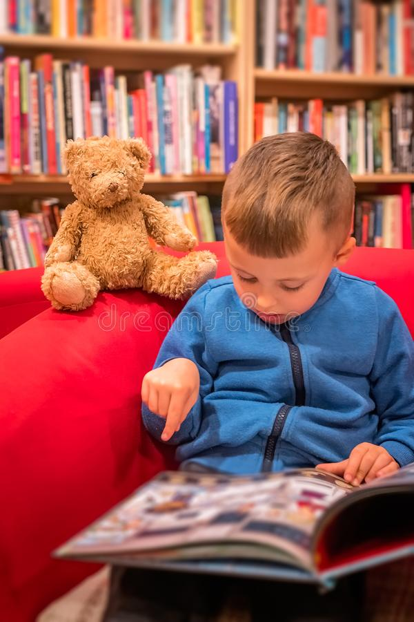 Boy browsing through book in a bookstore. Cute little Caucasian boy sitting in a chair with his favorite soft teddy bear toy and browsing through book in a small stock image
