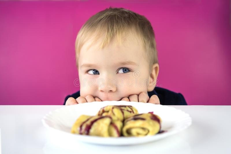 Cute little caucasian child boy hiding behind the table and looking over the table edge at a plate of food, a sweet dessert at l royalty free stock image