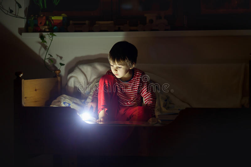 Cute little caucasian child, boy, reading book in bed stock photo