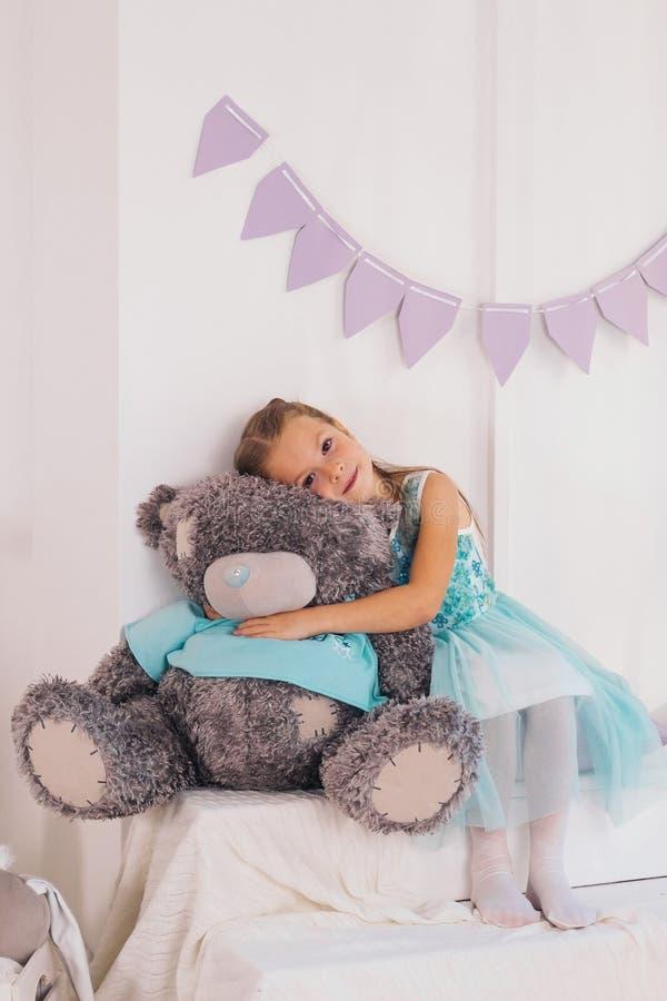 Little caucasian girl hugs big gray teddy bear. Cute little caucasian girl hugs big gray teddy bear royalty free stock image