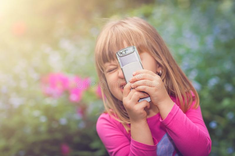 Little girl playing with her smartphone stock images