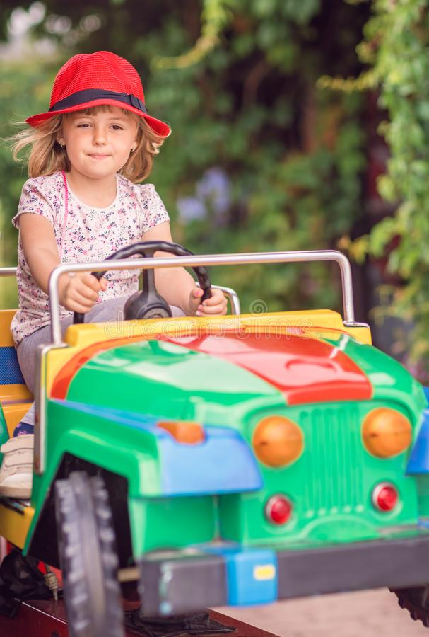 Cute girl driving toy car royalty free stock photo