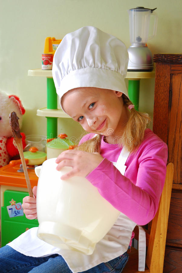 Cute little chef. Portrait of a beautiful cute little Caucasian girl child with happy smiling expression in her dirty face sitting in her toy kitchen mixing the royalty free stock image