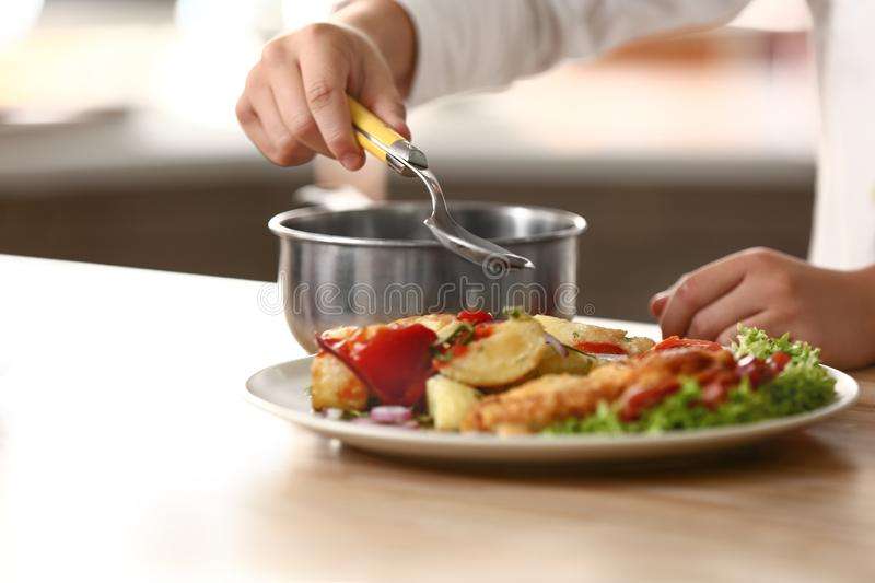 Cute little chef dressing tasty dish in kitchen, closeup stock photography