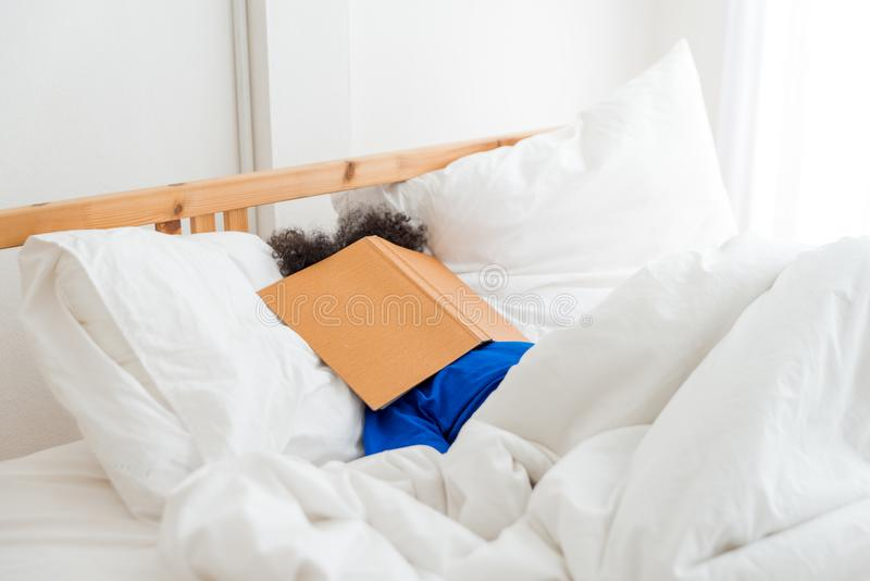 A cute little child African American girl sleeping and lazy when reading the book royalty free stock photography