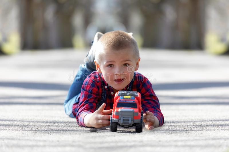 Cute little child, blonde toddler boy playing outdoors lying at street stock photography