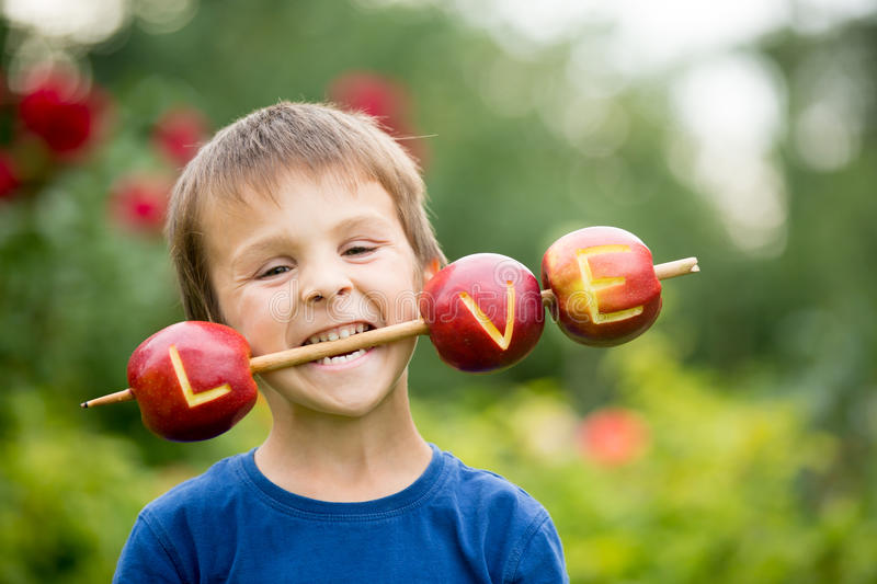 Cute little child, boy, holding a love sign, made from apples, l. Etter graved in the apple, smiling happily. happiness childhood love concept stock image