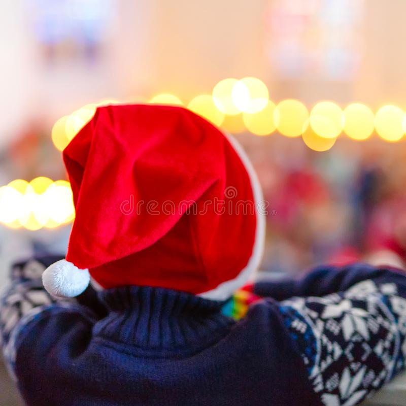 Cute little child on Christmas in a church. Praying kid boy with lights on background. Celebration of Xmas eve, big royalty free stock photography