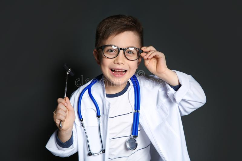 Cute little child in doctor uniform with reflex hammer on black royalty free stock images