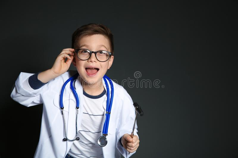 Cute little child in doctor uniform with reflex hammer on black background. royalty free stock photography