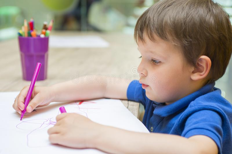 Cute little child is drawing with colorful felt-tip pens at home or kindergarten sitting at table in bright sunny play room. Cute little child is drawing with royalty free stock photography