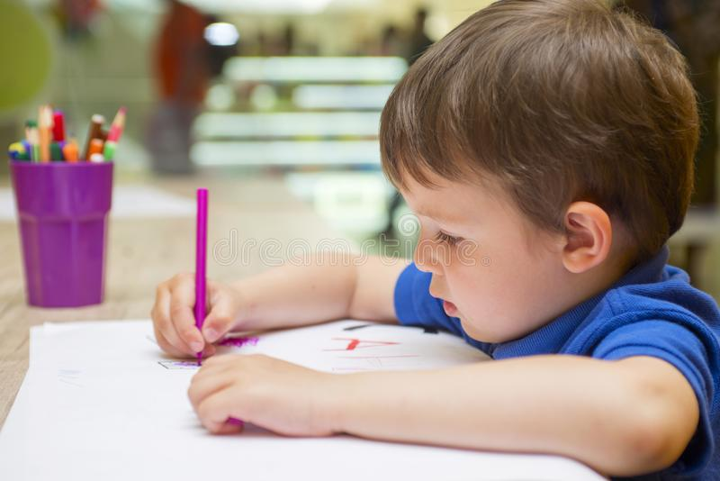 Cute little child is drawing with colorful felt-tip pens at home or kindergarten. Sitting at table in bright sunny playroom stock photo