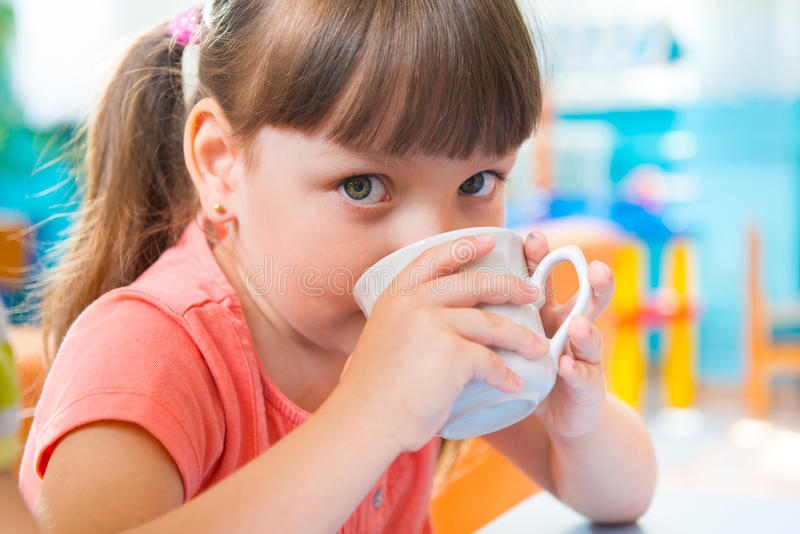 Cute little child drinking milk royalty free stock images