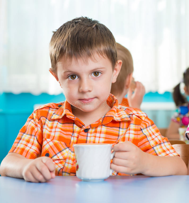 Cute little child drinking milk royalty free stock photo