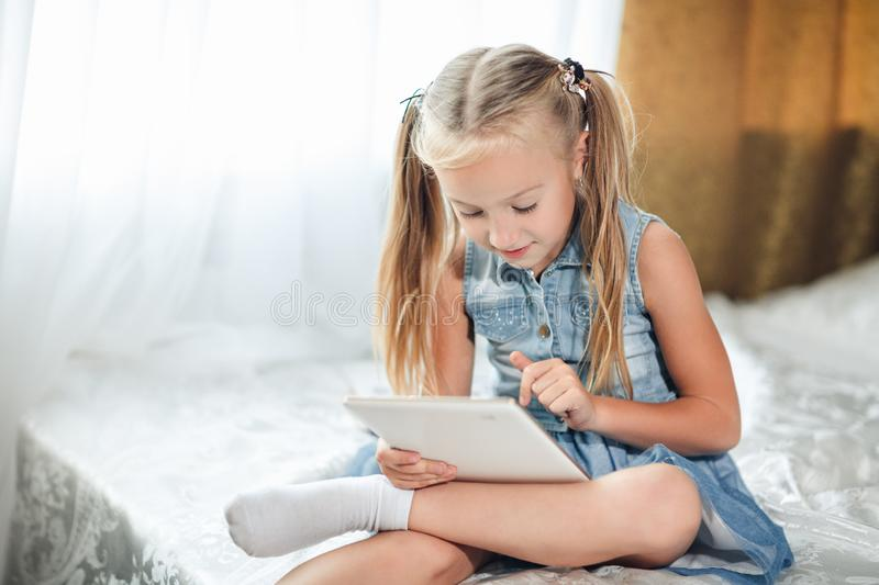 Cute little child girl blond in denim sundress lies in bed uses digital tablet. child playing on tablet pc royalty free stock photography
