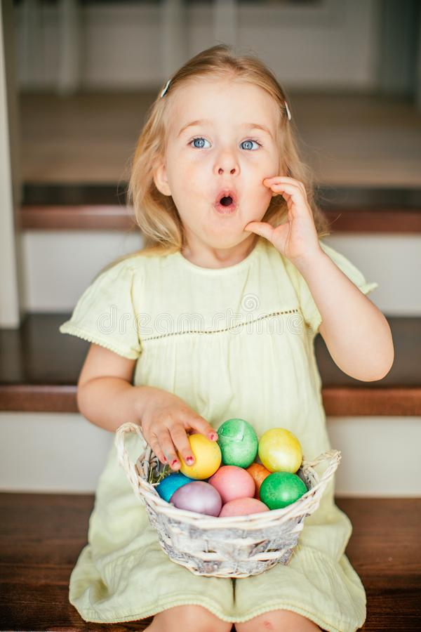 Cute little child girl with blonde hair on Easter day. Girl holding basket with painted eggs and sitting on the stairs at home royalty free stock photo