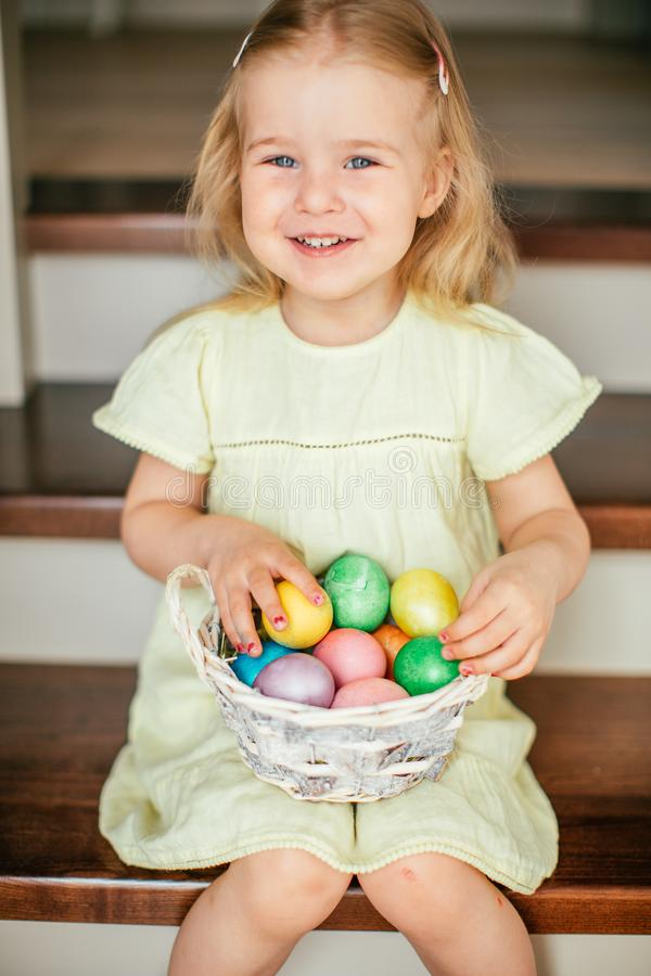 Cute little child girl with blonde hair on Easter day. Girl holding basket with painted eggs and sitting on the stairs at home royalty free stock image