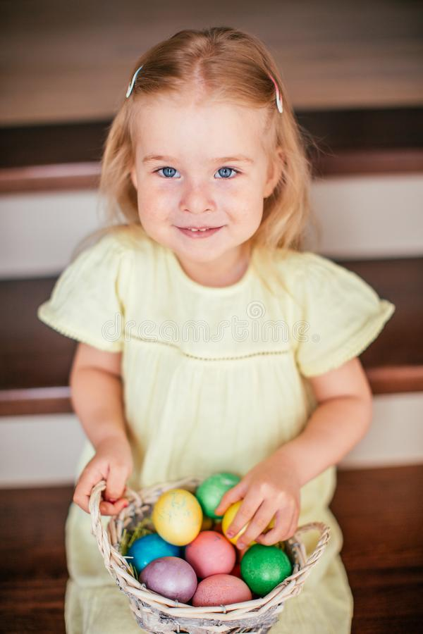 Cute little child girl with blonde hair on Easter day. Girl holding basket with painted eggs and sitting on the stairs at home stock photo