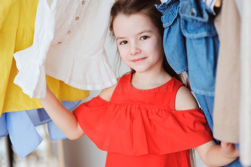 cute little child girl choosing new modern clothes in her wardrobe or store fitting room royalty free stock photo