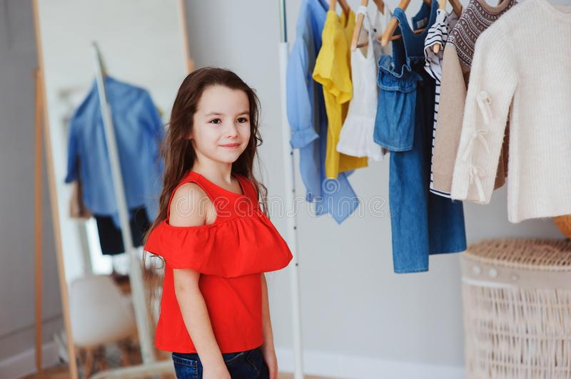 cute little child girl choosing new modern clothes in her wardrobe or store fitting room royalty free stock images