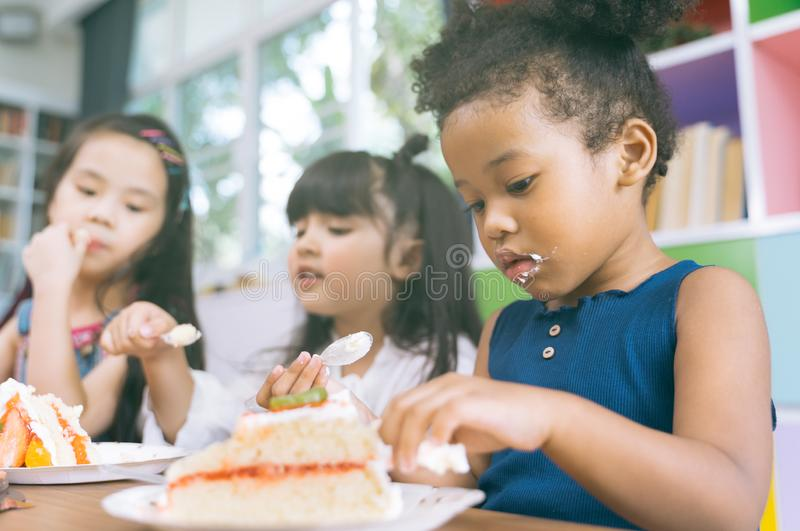 Cute little child girl with diversity friends eating cake together. kids eat dessert. royalty free stock photo