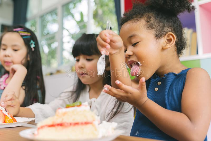 Cute little child girl with diversity friends eating cake together. kids eat dessert. royalty free stock photography