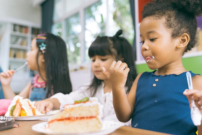 Cute little child girl with diversity friends eating cake together. kids eat dessert. stock photos