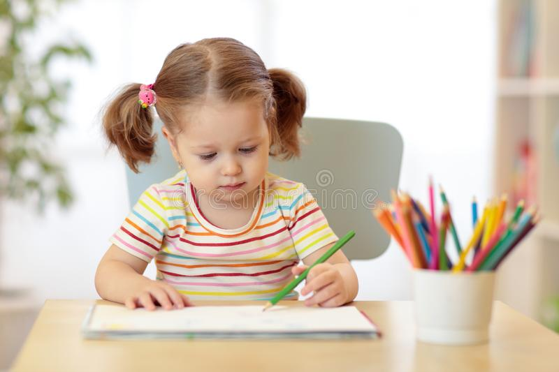 Cute little child girl drawing with pencils in daycare center royalty free stock photography