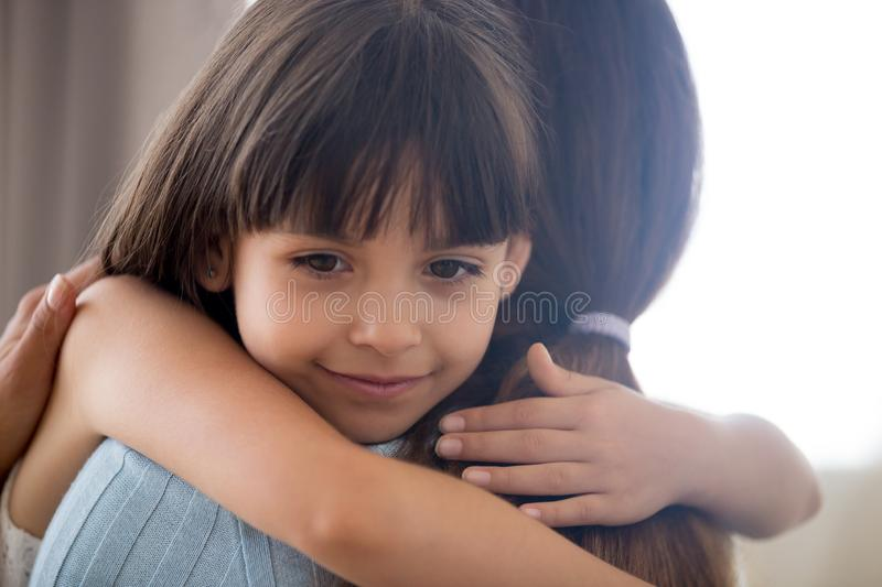 Cute little child girl embracing loving mother holding tight cud stock images