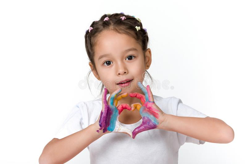 Little child girl with hands painted in colorful paint. Cute little child girl with hands painted in colorful paint make heart shape with love isolated on white stock image
