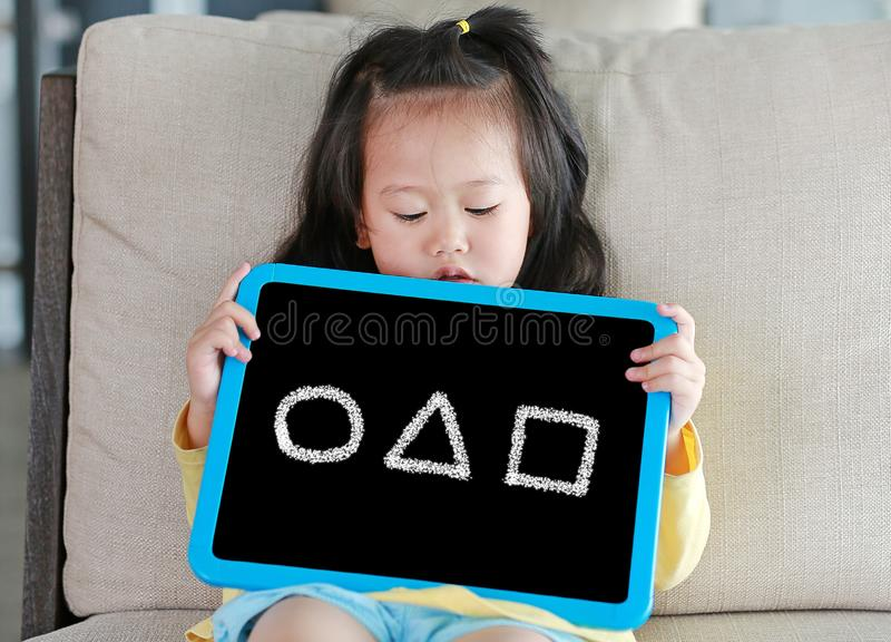 Cute little child girl holding blackboard showing image shape of circle triangle and square in library room stock photos