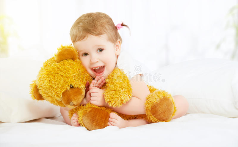Cute little child girl hugging teddy bear in bed. The cute little child girl hugging teddy bear in bed royalty free stock photography
