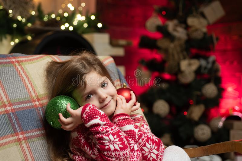 Cute little child girl play ornaments balls christmas tree. Kid enjoy winter holiday at home. Home filled joy. Cozy stock image
